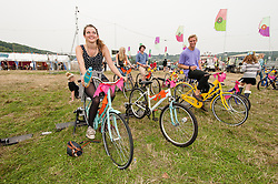 © Licensed to London News Pictures. 05/09/2014. Isle of Wight, UK. Festival goers at Bestival 2014 Day 2 Friday exercising on cycle machines while dance music plays loudly as an invigorating start to the day for a weekend of live music.  This weekend's headliners include Chic featuring Nile Rodgers, Foals and Outcast Photo credit : Richard Isaac/LNP