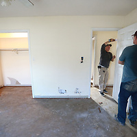 Divid Gillard, left, and Robert Faulkner begin removing doors after all the carpet has been removed from a house in Willow Creek before they can replace the dry wall throughout the house.