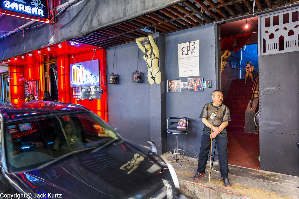 "4 JUNE 2013 - BANGKOK, THAILAND:  A tout in the doorway of the BB Bar, which calls itself a ""fetish and bondage"" bar in the Patpong Night Bazaar in Bangkok. Patpong was one of Bangkok's notorious red light districts but has been made over as a night market selling clothes, watches and Thai handicrafts. The old sex oriented businesses still exist but the area is now better known for its night shopping.      PHOTO BY JACK KURTZ"