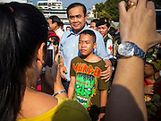 "11 JANUARY 2014 - BANGKOK, THAILAND: General PRAYUTH CHAN-OCHA, Commender in Chief of the Thai Royal Army, poses for photos with a Thai boy during a Children's Day fair in Bangkok. The Royal Thai Army hosted a ""Children's Day"" event at the 2nd Cavalry King's Guard Division base in Bangkok. Children had an opportunity to look at military weapons, climb around on tanks, artillery pieces and helicopters and look at battlefield medical facilities. The Children's Day fair comes amidst political strife and concerns of a possible coup in Thailand. Gen Prayuth has issued mixed signal on a coup at one point saying there wouldn't be one, and later saying he wouldn't talk about a possible coup. Earlier in the week, the Thai army announced that movements of armored vehicles through Bangkok were not in preparation of a coup, but were moving equipment into position for Children's Day.       PHOTO BY JACK KURTZ"