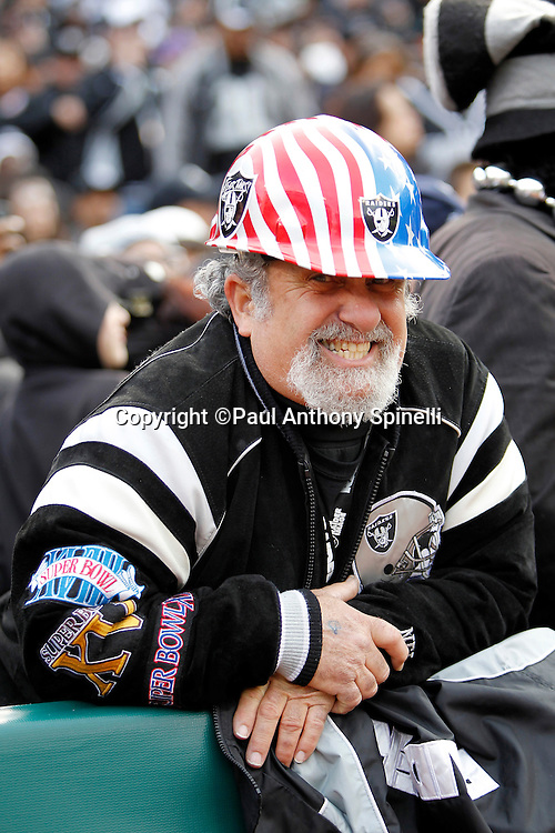 A fan wears Raiders gear and a stars and stripes helmet as the Oakland Raiders take the field during the NFL week 16 football game against the Indianapolis Colts on Sunday, December 26, 2010 in Oakland, California. The Colts won the game 31-26. (©Paul Anthony Spinelli)