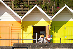 © Licensed to London News Pictures. 19/07/2016. Scarborough Bay UK. Picture shows a couple enjoying their beach hut this morning in Scarborough. Temperature's are expected to reach a record high today.Photo credit: Andrew McCaren/LNP