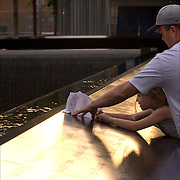 At sunset, father is helping his daughter at the memorial to trace the name of a love one who lost their life on 9/11/01. <br />