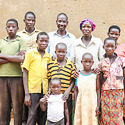 CAPTION: Florence Agabo with her husband Dominic Ekaju and their children. Dominic is a primary school teacher, but the family also farm in order to supplement their income. LOCATION: Apapai Parish, Otuboi Sub-county, Kalaki County, Kaberamaido District, Uganda. INDIVIDUAL(S) PHOTOGRAPHED: From left to right: Damali Ilimu, John Ekaju, Abraham Ekeju, Dominic Ekaju, Francis Eyunu, Innocent Emalu, Florence Agabo, Pekula Adiao, Sarah Amwodo and Pascal Akora.