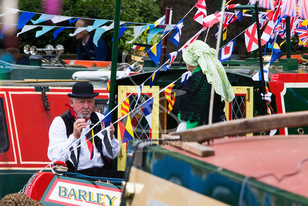 Little Venice, London, April 30th 2017. Narrowboaters from all over the UK gather for the annual Canalway Cavalcade, held on the May Day Bank holiday weekend, organised by the Inland Waterways Association, where boaters get the chance to display their immaculately prepared and brightly painted craft as well as compete in various manoeuvring tests. PICTURED: A soul in period dress await the blessing of the fleet by Father Gary Bradley of the Little Venice Parish.