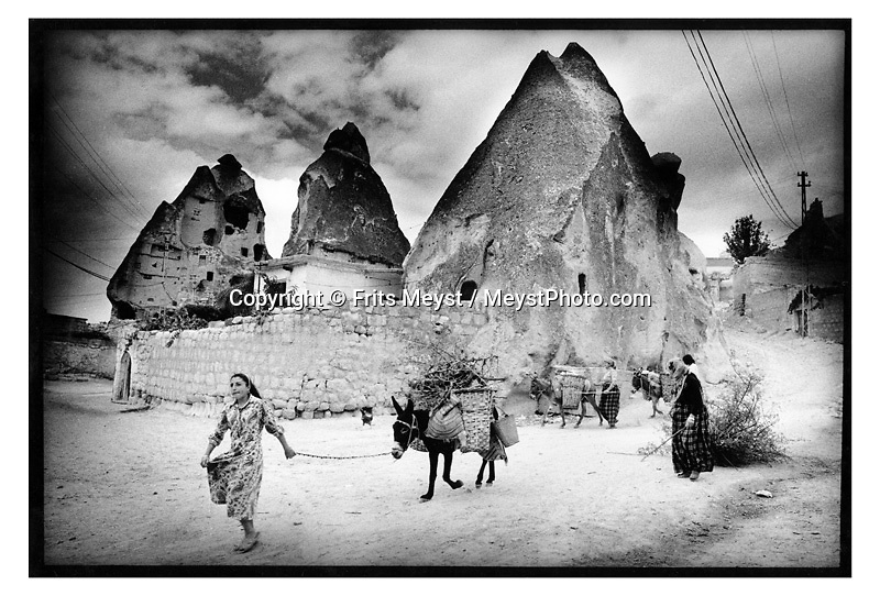 GOREME, CAPPADOCIA, TURKEY, 2000.  Women pass in front of their cave house in the rock with a donkey and fire wood. . Traditional life in Cappadocia has come under heavy strain, due to the increased tourism. the young generation is not interested in working the fields if they can work in a carpetshop, restaurant or bar. Therefore centuries old skills and habits will die with the elderly. Cappadocia is knowns for its landscape with conical shaped rock formations and cave dwellings in which the local people live. ©Photo by Frits Meyst/Adventure4ever.com