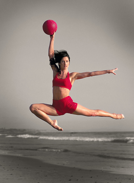 Girl leaping in the air with red ball on Carlsbad State Beach, CA.