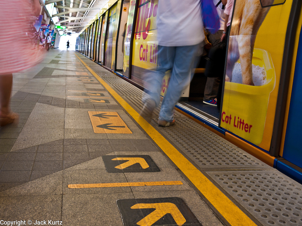 14 JULY 2011 - BANGKOK, THAILAND:   People rush to get on the train on the Sukhmvit line of the BTS Skytrain in Bangkok. The Bangkok Mass Transit System, commonly known as the BTS Skytrain, is an elevated rapid transit system in Bangkok, Thailand. It is operated by Bangkok Mass Transit System Public Company Limited (BTSC) under a concession granted by the Bangkok Metropolitan Administration (BMA). The system consists of twenty-three stations along two lines: the Sukhumvit line running northwards and eastwards, terminating at Mo Chit and On Nut respectively, and the Silom line which plies Silom and Sathon Roads, the Central Business District of Bangkok, terminating at the National Stadium and Wongwian Yai. The lines interchange at Siam Station and have a combined route distance of 55 km.   PHOTO BY JACK KURTZ