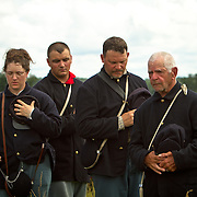 From left, Wendi Dowler, of Latrobe, PA, David Kukura, of Black Lick, PA, Rex Lichtenfels, of New Florence, PA, and Chuck Patz, of New Florence, PA, all living historians representing the Union Signal Corps listen as Taps is played at the conclusion of the Pickett's Charge Commemorative March, during the Sesquicentennial Anniversary of the Battle of Gettysburg, Pennsylvania on Wednesday, July 3, 2013.  The march was an opportunity to follow in the footsteps of Union or Confederate soldiers by walking with living historians and park rangers along the paths during the famously ill-fated Pickett's Charge, which brought to a close The Battle of Gettysburg when the Union Army repelled their advance. Taps was first thought to have been played at a military funeral or memorial service in 1862, at the burial of a Union soldier.  The Battle of Gettysburg lasted from July 1-3, 1863 resulting in over 50,000 soldiers killed, wounded or missing.  John Boal Photography