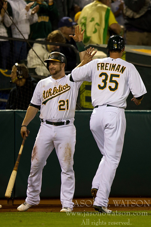 OAKLAND, CA - JULY 05:  Nate Freiman #35 of the Oakland Athletics is congratulated by Stephen Vogt #21 after scoring a run against the Toronto Blue Jays during the eighth inning at O.co Coliseum on July 5, 2014 in Oakland, California. The Oakland Athletics defeated the Toronto Blue Jays 5-1.  (Photo by Jason O. Watson/Getty Images) *** Local Caption *** Nate Freiman; Stephen Vogt