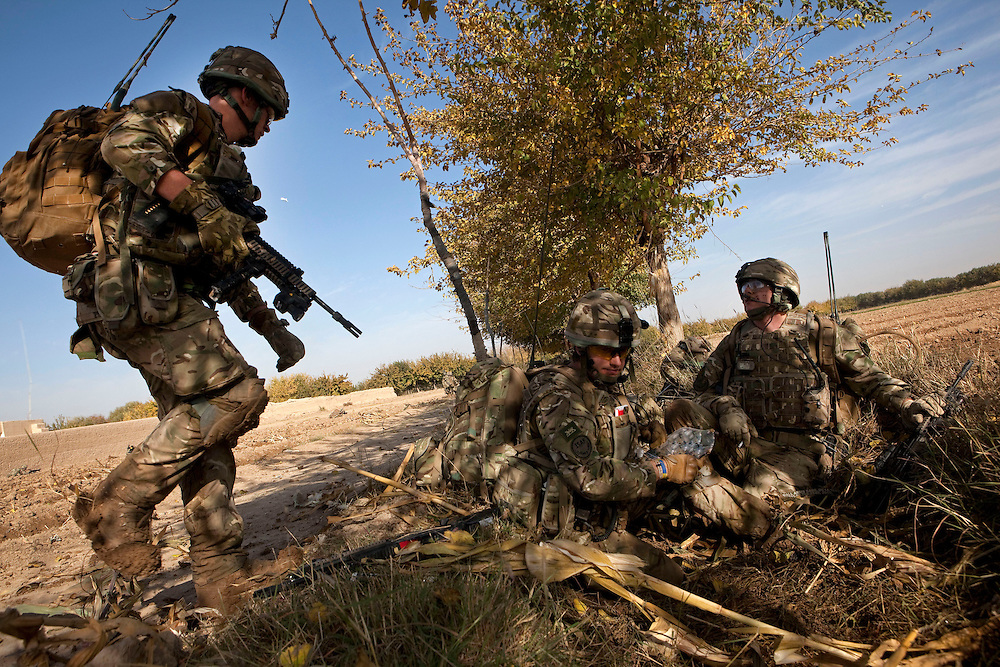 British soldiers from 1PWRR (Princess of Waless Royal  Regiment) and from 3 SCOTS (The Black Watch) recompose themselves after a MEDEVAC helicopter takes off carrying Private Stephen Bainbridge, aged 25, from Kirkcaldy was gravely wounded by an IED explosion just inside the doorway of a nearby compound. The blast traumatically amputated his right leg and damaged his right so badly that it too later had to be amputated. His life was saved by the swift actions of Cpl John Goodie (21) a medic with 1 PWRR (The Princess of Wales's Royal Regiment) who applied tourniquets and first field dressings to get the bleeding under control. Private Chis Watson (21) also assisted in the treatment whilst reassuring the casualty and keeping him alert and responsive.  Once he had been stabilized the men CASEVAC'd Private Bainbridge to the MERT helicopter and he was rushed to Bastion Field Hospital.  Loya Manda, Nad e Ali, Helmand Province, Afghanistan on the 11th of November 2011.