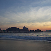 Praia de Copacabana at sunrise. Copacabana beach, one of the world's most famous urban beaches at sunrise with Sugar Loaf Mountain in the distance. The beach and hotel strip stretches for 1.5 miles (4km) from the Morro do Leme at the Northern end, to Arpoador at the South. Copacabana beach, Rio de Janeiro,  Brazil. 13th August 2010. Photo Tim Clayton..