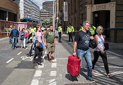 © Licensed to London News Pictures. 04/06/2017. London, UK. Tourists are escorted out of the police cordon at London Bridge after being stuck there overnight. Seven people are reported to have been killed after a white van veered off the road and hit a number of pedestrians. Photo credit: Rob Pinney/LNP