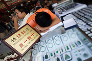 "Panjiayuan weekend market. Jade dealer with ""no-fake-guarantee"" having a nap."