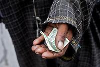 A beggar asks for money, in the bazaar, Kargil