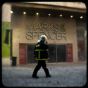 A firefighter walks in the deserted Ermou street at the centre of Athens. <br /> <br /> Following the murder of a 15 year old boy, Alexandros Grigoropoulos, by a policeman on 6 December 2008 widespread riots, protests and unrest followed lasting for several weeks and spreading beyond the capital and even overseas<br /> <br /> When I walked in the streets of my town the day after the riots I instantly forgot the image I had about Athens, that of a bustling, peaceful, energetic metropolis and in my mind came the old photographs from WWII, the civil war and the students uprising against the dictatorship. <br /> <br /> Thus I decided not to turn my digital camera straight to the destroyed buildings but to photograph through an old camera that worked as a filter, a barrier between me and the city.