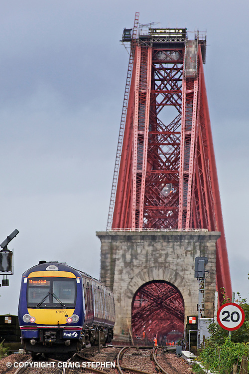 A commuter train crosses the Forth rail bridge leaving North Queensferry station, Fife, Scotland