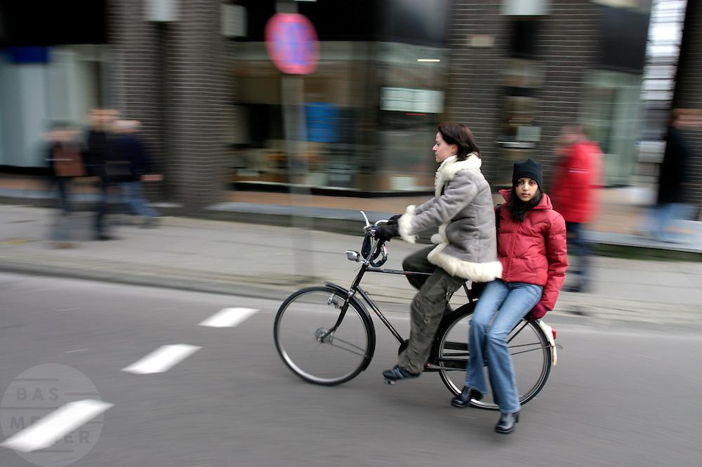 Een meisje fietst met een ander meisje achterop door de Vijzelstraat in Amsterdam.<br /> <br /> A girl is cycling with another girl on the back of the bike at the Vijzelstraat Amsterdam.