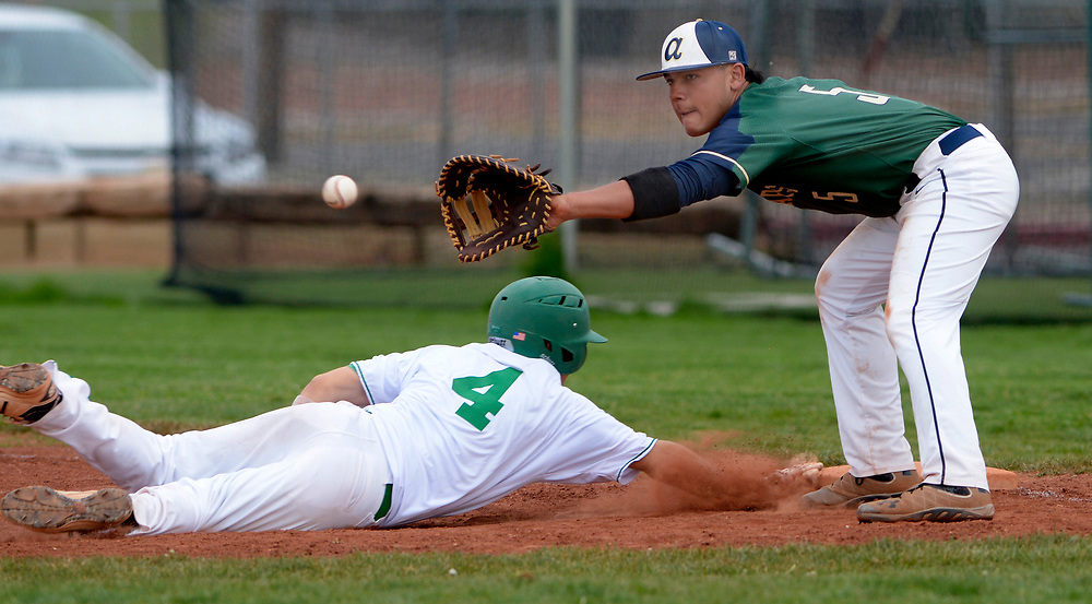 gbs041117t/SPORTS -- Albuquerque High's Robby Herrera, 4, dives back to first base under the throw to Atrisco Heritage first baseman Vicente Trujillo in the fifth inning of the game  at Albuquerque High on Tuesday, April 11, 2017.(Greg Sorber/Albuquerque Journal)