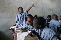 May, 2005, Cotonou, Benin --- Boy Raising Hand in Classroom of Private Elementary School --- Image by © Owen Franken/Corbis