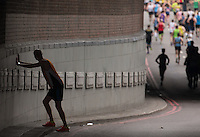 An athlete stretches against a wall at the Blackfriars underpass. The Virgin Money London Marathon, Sunday 26th April 2015.<br /> <br /> Photo: Jed Leicester for Virgin Money London Marathon<br /> <br /> For more information please contact Penny Dain at pennyd@london-marathon.co.uk