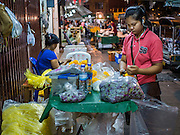 30 JUNE 2016 - BANGKOK, THAILAND: A vendor makes flower garlands at a sidewalk stall near Pak Khlong Talat. Sidewalk vendors around Pak Khlong Talat, Bangkok's famous flower market, face eviction if they reopen on July 1. As a part of the military government sponsored initiative to clean up Bangkok, city officials have been trying to shut down the sidewalk vendors around the flower market. The vendors were supposed to be gone by the end of March, but city officials relented at the last minute with a compromise allowing vendors to stay until June 30. When vendors dismantled their booths after business on June 30, they weren't sure if they will be allowed to reopen July 1. Some vendors have moved to new locations approved by the government but many have not because they can't afford the higher rents in the new locations.     PHOTO BY JACK KURTZ
