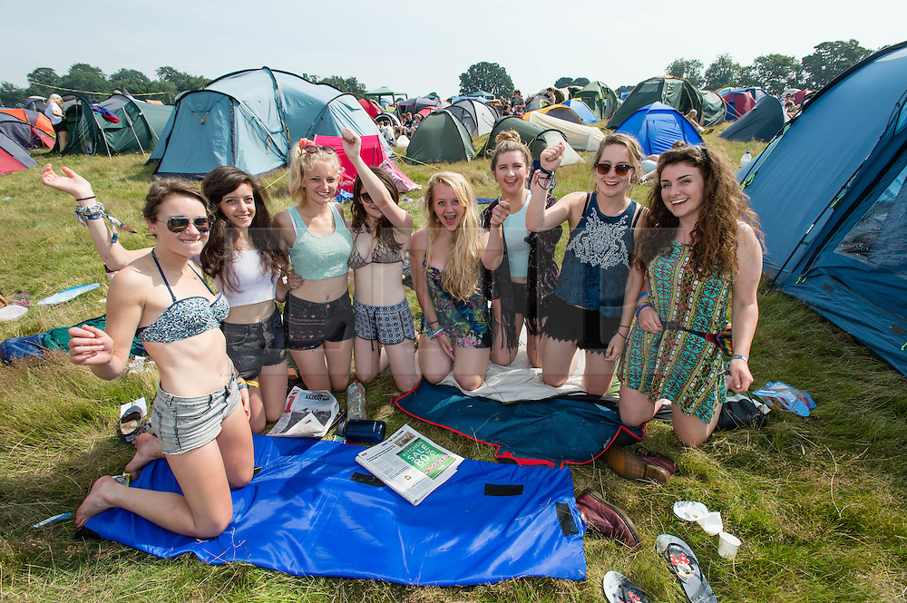 © Licensed to London News Pictures. 18/07/2014. Southwold, UK.    A group of young female festival goers in amongst their campsite tents on a hot sunny morning at  Latitude Festival 2014 Day 1.  Today is expected to be the hottest day of the year with temperatures forecast to reach 32 degrees centigrade.   Latitude is an British annual music festival.  Photo credit : Richard Isaac/LNP