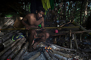 A Maniq man called Boy prepares his blowpipe for a hunting trip.<br /> <br /> Evidence suggests that the Maniq, a Negrito tribe of hunters and gatherers, have inhabited the Malay Peninsula for around 25,000 years. Today a population of approximately 350 maniq remain, marooned on a forest covered mountain range in Southern Thailand. Whilst some have left their traditional life forming small villages, the majority still live the way they have for millennia, moving around the forest following food sources. <br /> <br /> Quiet and reclusive they are little known even in Thailand itself but due to rapid deforestation they are finding it harder to survive on the forest alone and are slowly being forced to move to its peripheries closer to Thai communities.