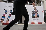Woman's legs and arm with construction hoarding, a part of the forthcoming fashion label, Valentino Garavani's new shop in New Bond Street, central London.