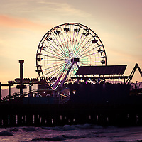 Photo of Santa Monica Pier Ferris Wheel at sunset in Los Angeles County Southern California. Santa Monica Pier is a landmark that has an amusement park with a ferris wheel, roller coaster, restaurants, and other attractions.