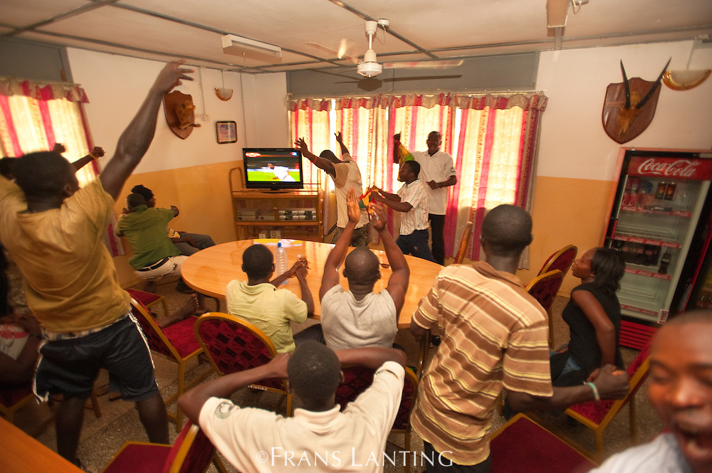 People cheering for Ghana during World Cup soccer match, Mole N.P., Ghana