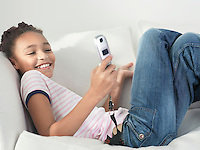 Smiling Girl lying on sofa using Cell Phone side view