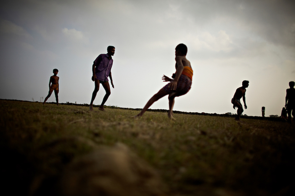 Boys play Kabaddi in the fields of Chaar Patilla, by the Bay of Bengal...This area in the south of Bangladesh has been called ground zero of climate-change due to heavy river and ocean erosion. The lowlying area is also hugely affected by cyclones and rising sea-levels...By the Mouth of Ganges, at the Bay of Bengal is the Island of Bhola. This home of about two million people is considered to be ground zero of climate change. Half the island has disappeared in the past 40 years, and according to scientists the pace is not going to slow down. People pack up and leave as the water get closer. Some to a nearby embankment, while those with enough money move further inland, but for most life move on until the inevitable. It's always about survival for the people in one of the worlds poorest countries...Photo by: Eivind H. Natvig/MOMENT