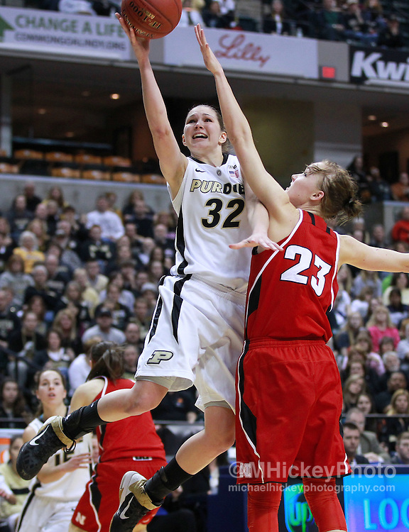 March 04, 2012; Indianapolis, IN, USA; Purdue Boilermakers guard/forward Sam Ostarello (32) shoots the ball over Nebraska Cornhuskers forward Emily Cady (23)  during the finals of the 2012 Big Ten Tournament at Bankers Life Fieldhouse. Purdue defeated Nebraska 74-70 in 2OT. Mandatory credit: Michael Hickey-US PRESSWIRE