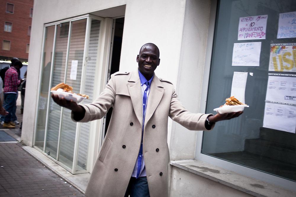 Un ragazzo sorride ironico dopo la distribuzione del pasto. Esterno ex palazzine olimpiche.