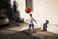 PALERMO, 29 LUGLIO 2015: Un ragazzo del GREST (Gruppo Estivo) gioca a calcio nel cortile della Parrocchia di Santa Lucia Borgovecchio, a Palermo il 29 luglio 2015.