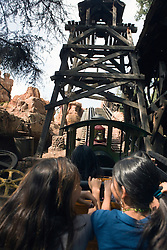 Two girls ride in the front seat of a wooden roller coaster, Disneyland Resort, Anaheim, California, United States of America.