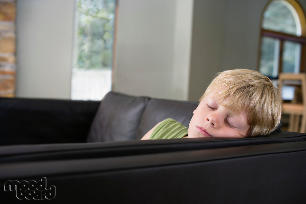 Young boy (5-6) sleeping on sofa