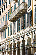 Woman at window above arcades and traditional lanterns of famous Liston at the Spianada in Kerkyra, Corfu Town, Greece