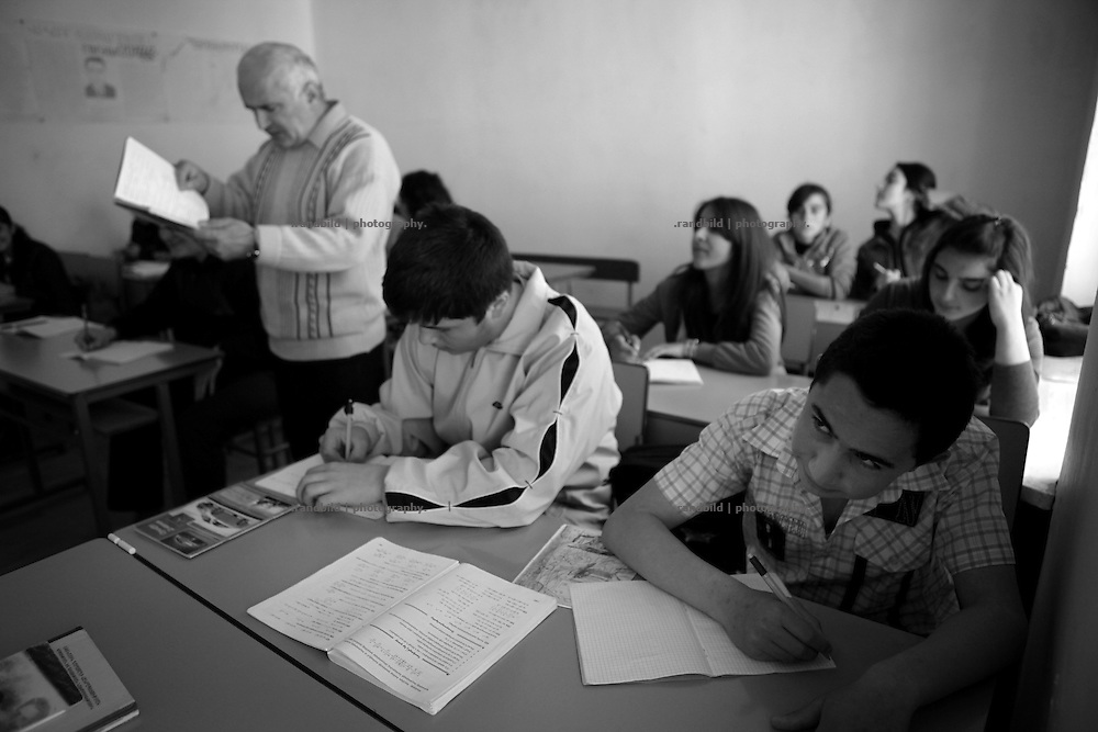 "Classroom during a lesson in a public school. This image is part of the photoproject ""The Twentieth Spring"", a portrait of caucasian town Shushi 20 years after its so called ""Liberation"" by armenian fighters. In its more than two centuries old history Shushi was ruled by different powers like armeniens, persians, russian or aseris. In 1991 a fierce battle for Karabakhs independence from Azerbaijan began. During the breakdown of Sowjet Union armenians didn´t want to stay within the Republic of Azerbaijan anymore. 1992 armenians manage to takeover ""ancient armenian Shushi"" and pushed out remained aseris forces which had operate a rocket base there. Since then Shushi became an ""armenian town"" again. Today, 20 yeras after statement of Karabakhs independence Shushi tries to find it´s opportunities for it´s future. The less populated town is still affected by devastation and ruins by it´s violent history. Life is mostly a daily struggle for the inhabitants to get expenses covered, caused by a lack of jobs and almost no perspective for a sustainable economic development. Shushi depends on donations by diaspora armenians. On the other hand those donations have made it possible to rebuild a cultural centre, recover new asphalt roads and other infrastructure. 20 years after Shushis fall into armenian hands Babies get born and people won´t never be under aseris rule again. The bloody early 1990´s civil war has moved into the trenches of the frontline 20 kilometer away from Shushi where it stuck since 1994. The karabakh conflict is still not solved and could turn to an open war every day. Nonetheless life goes on on the south caucasian rocky tip above mountainious region of Karabakh where Shushi enthrones ever since centuries."