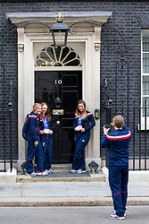 © Licensed to London News Pictures. 18/03/2014. London, UK. Medal winning visually impaired skier, Jade Etherington (2L) and her skiing guide Caroline Powell (R), have their picture taken in front of the iconic door of number 10 Downing Street during a visit by the British Winter Paralympic team to meet the British Prime Minister David Cameron after their return from Sochi today (18/03/2014). Photo credit: Matt Cetti-Roberts/LNP