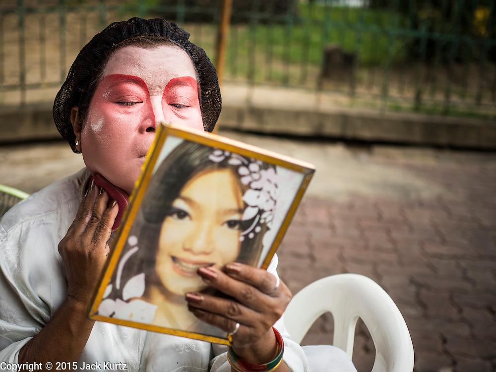 """14 MAY 2015 - BANGKOK, THAILAND:  A performer puts on her makeup before going on stage at the Pek Leng Keng Mangkorn Khiew Shrine in the Khlong Toey slum in Bangkok. Chinese opera was once very popular in Thailand, where it is called """"Ngiew."""" It is usually performed in the Teochew language. Millions of Chinese emigrated to Thailand (then Siam) in the 18th and 19th centuries and brought their culture with them. Recently the popularity of ngiew has faded as people turn to performances of opera on DVD or movies. There are still as many 30 Chinese opera troupes left in Bangkok and its environs. They are especially busy during Chinese New Year and Chinese holiday when they travel from Chinese temple to Chinese temple performing on stages they put up in streets near the temple, sometimes sleeping on hammocks they sling under their stage. Most of the Chinese operas from Bangkok travel to Malaysia for Ghost Month, leaving just a few to perform in Bangkok.      PHOTO BY JACK KURTZ"""