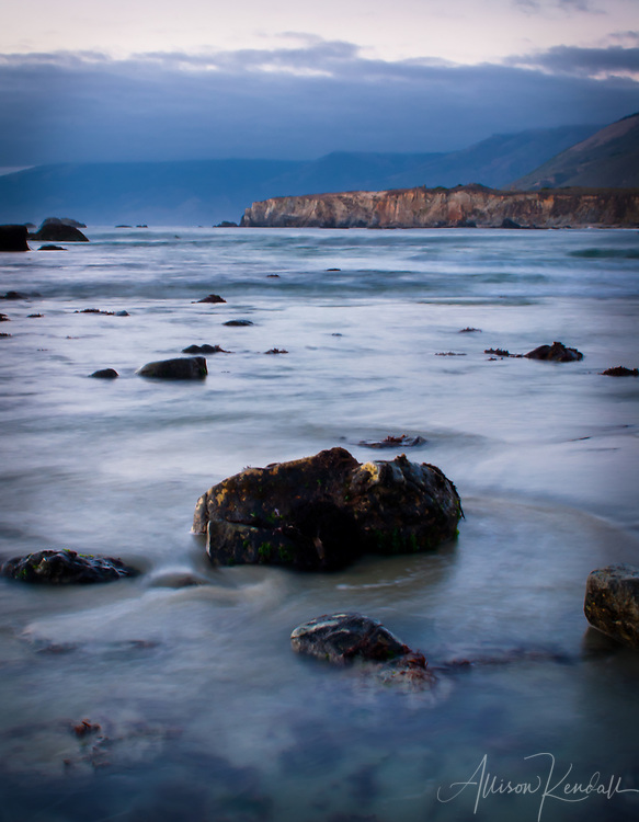 A long-exposure captures the soft flow of water in the last light of an October evening at a remote beach in Big Sur