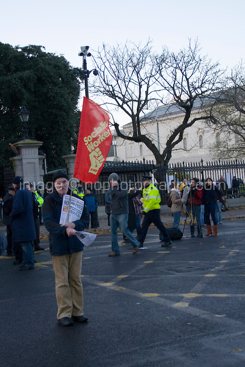 Protesters march outside government buildings in Dublin Ireland as part of a campaign organised by the Irish Congress of Trade Unions, man with Socialist Workers Party flag