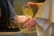 A priest pours water on a parishioner's foot during a Holy Thursday liturgy. The washing of feet is a ritual enactment of Jesus Christ washing the feet of his disciples at the Last Supper. (Sam Lucero photo)