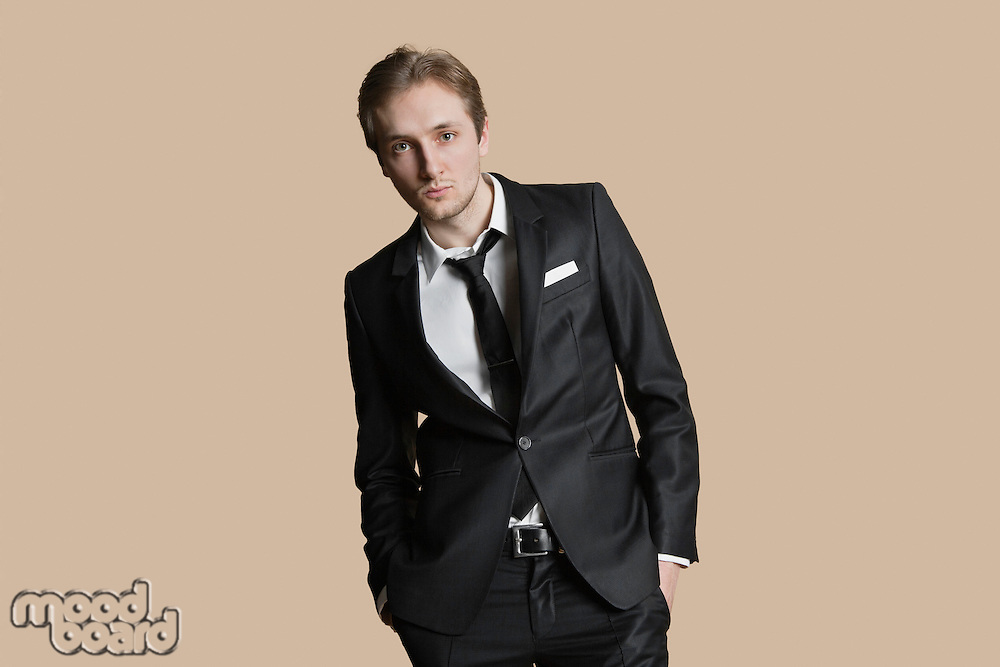 Portrait of young businessman with hands in pockets over colored background