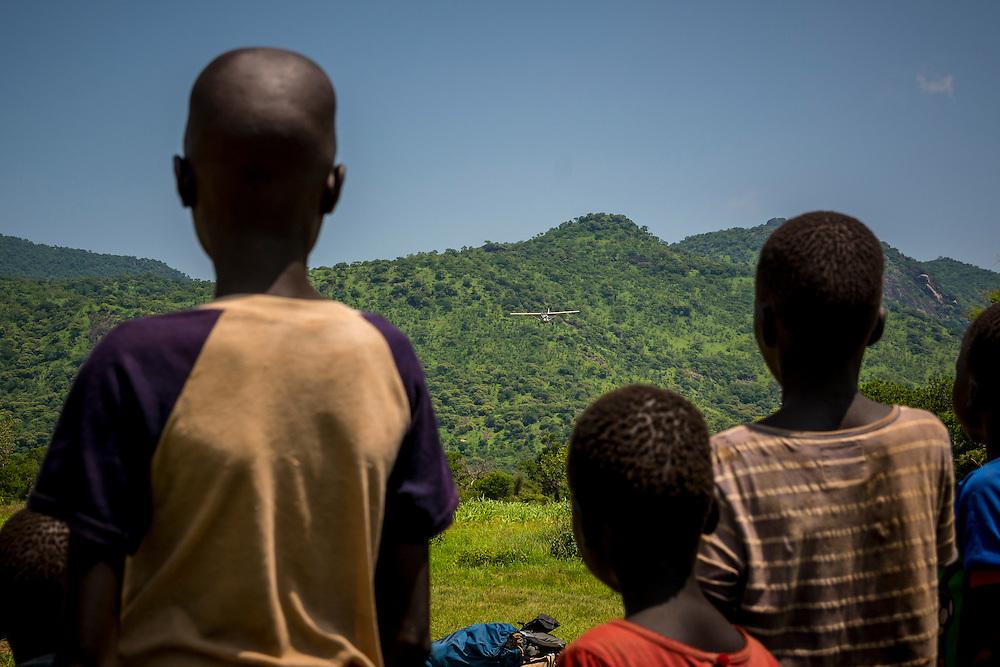 Children in Lokitok, South Sudan watch as an AIM Air plane approaches.