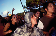 Teenagers, one hooded pulling aggressive face in dancing crowd, Istanbul, Turkey, 2000s.