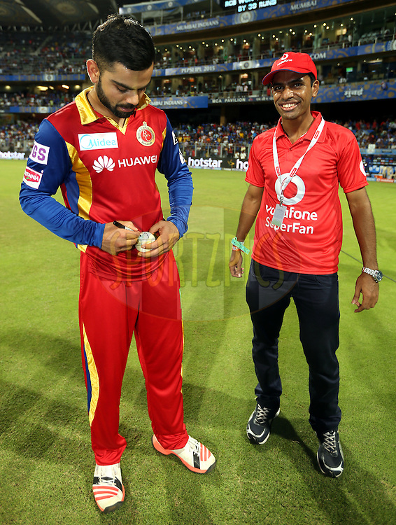 Royal Challengers Bangalore captain Virat Kohli signs the match ball during the presentation of the match 46 of the Pepsi IPL 2015 (Indian Premier League) between The Mumbai Indians and The Royal Challengers Bangalore held at the Wankhede Stadium in Mumbai, India on the 10th May 2015.<br /> <br /> Photo by:  Sandeep Shetty / SPORTZPICS / IPL