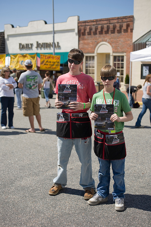 Austin McKee, 14, left, and Casey Hillenburg, 12, son of Rockingham Speedway owner Andy Hillenburg, were selling programs for the upcoming Carolina 200 during Thunderfest in downtown Rockingham, N.C.